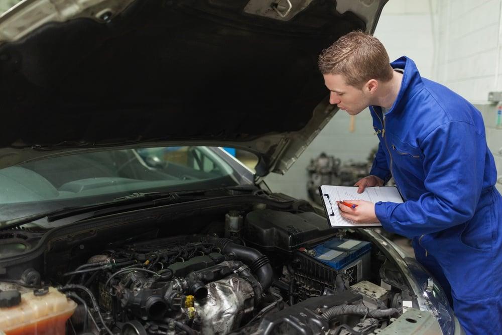 Male mechanic writing on clipboard while examining car engine